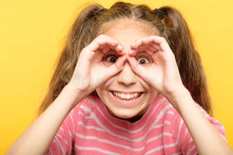 Prismáticos juguetones alegres divertidos de la mano de la mirada de la muchacha imágenes de archivo libres de regalías