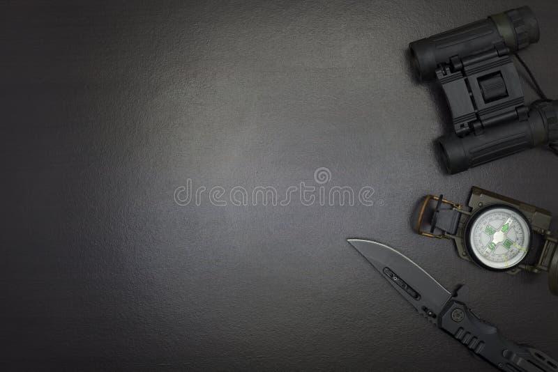 prismáticos, navaja de bolsillo, compás, en fondo de madera oscuro fotografía de archivo