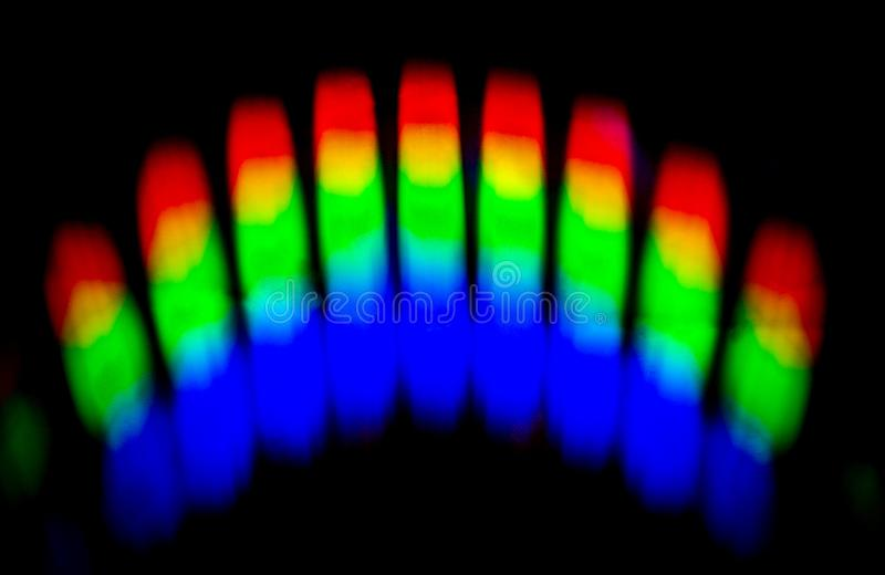 A Prism Reflects Vibrant Colors onto a Dark Wall. A prism is a transparent optical element with flat, polished surfaces that refract light causing light of royalty free stock photography
