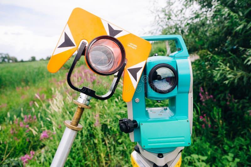 Prisme orange de théodolite et station totale de examen bleue d'équipement sur un fond de lac image stock