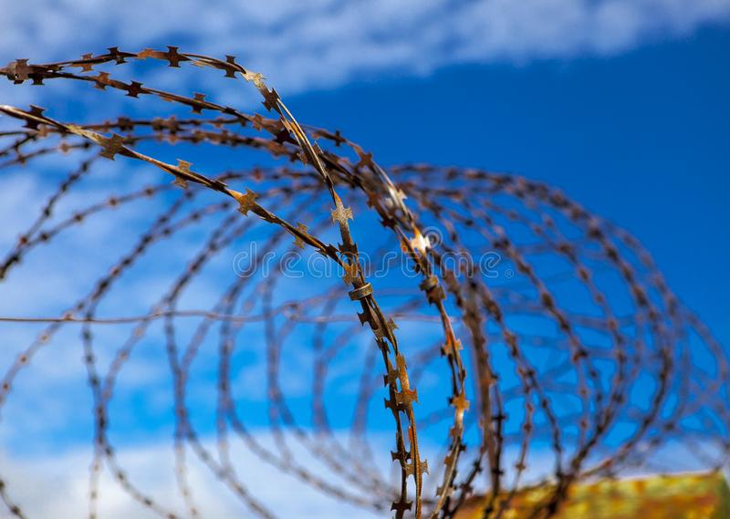 Prison. Barbed wire. Barbed wire on blue sky background with white clouds. Wire boom. Military conflict . Syria. stock photos