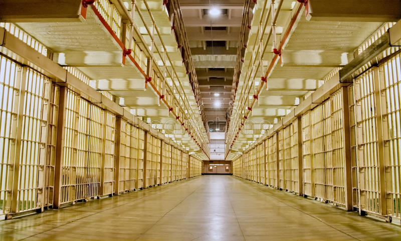 Prison cell block with cells on both sides. Prison cell block corridor with cells on both sides royalty free stock images