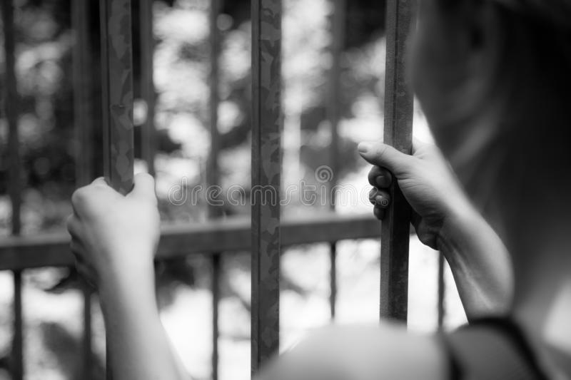 Prison cell: Close up of hands in jail royalty free stock photography