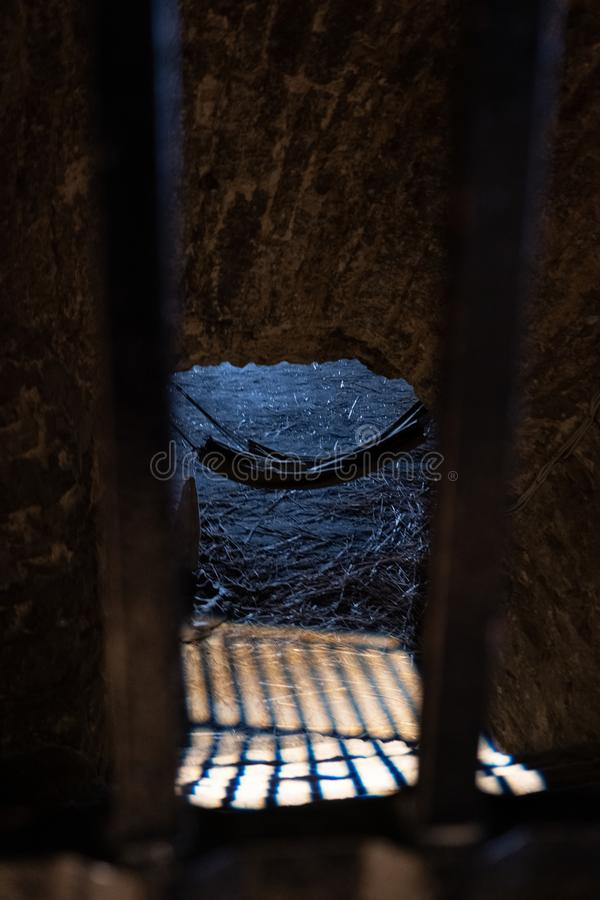 A prison cell with a hammock and sun rays penetrating through the locked bars stock images