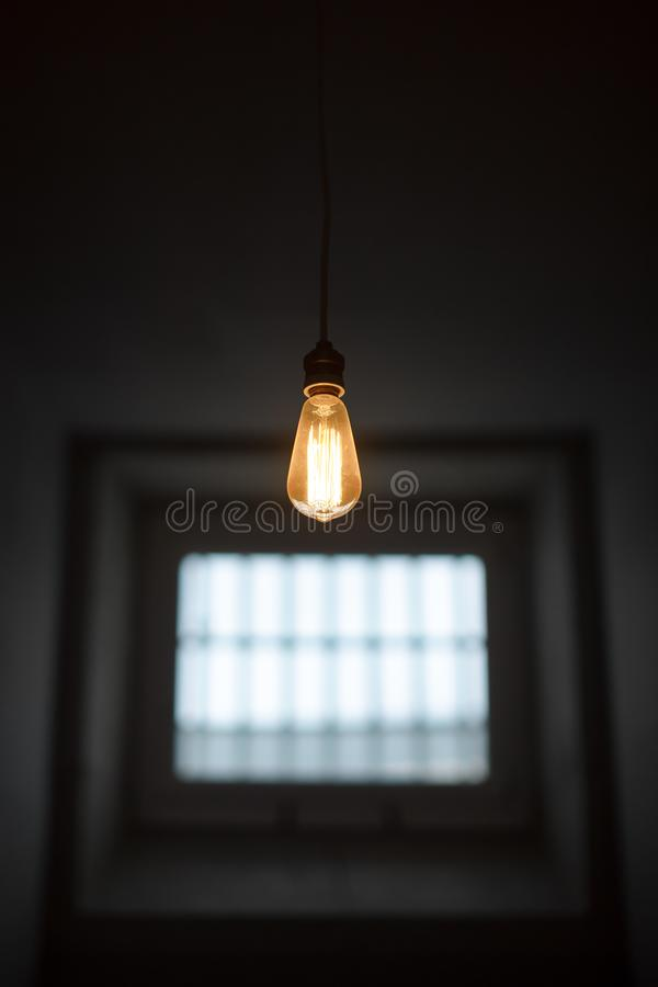 Prison cell with old lamp and small window stock photos