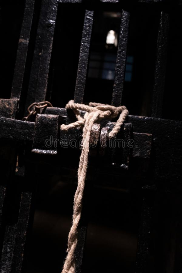 A prison cell with the prison doors locked with a tied rope knot and a chain royalty free stock photos