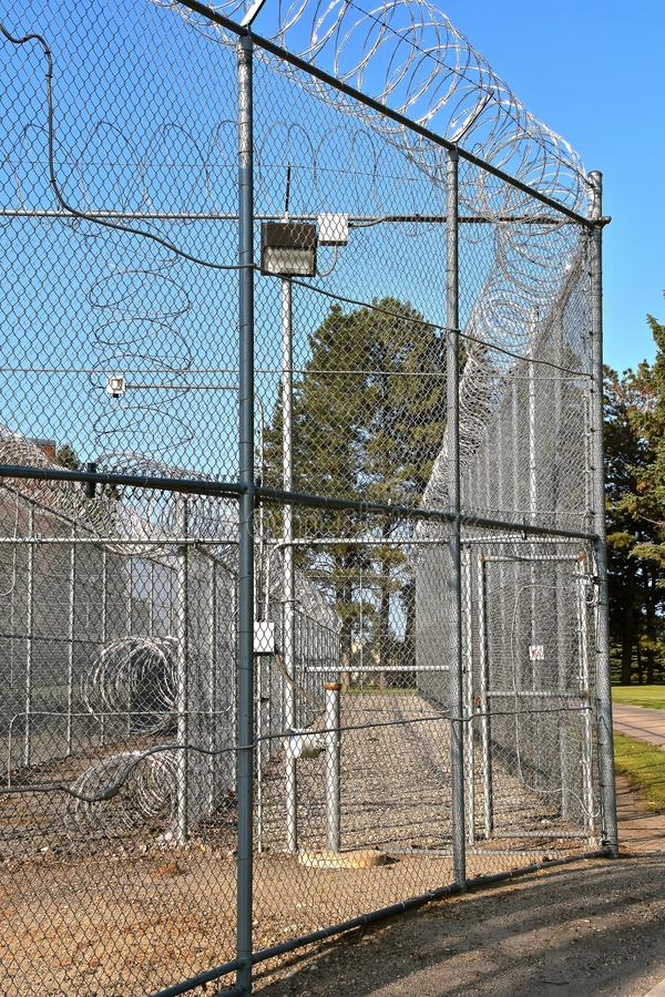 Prison fence and security camera. A camera and security concentina fence surround a prison facility royalty free stock photography