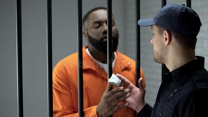 Prison guard giving afro-american imprisoned male dose of drugs illegal activity. Stock photo stock images