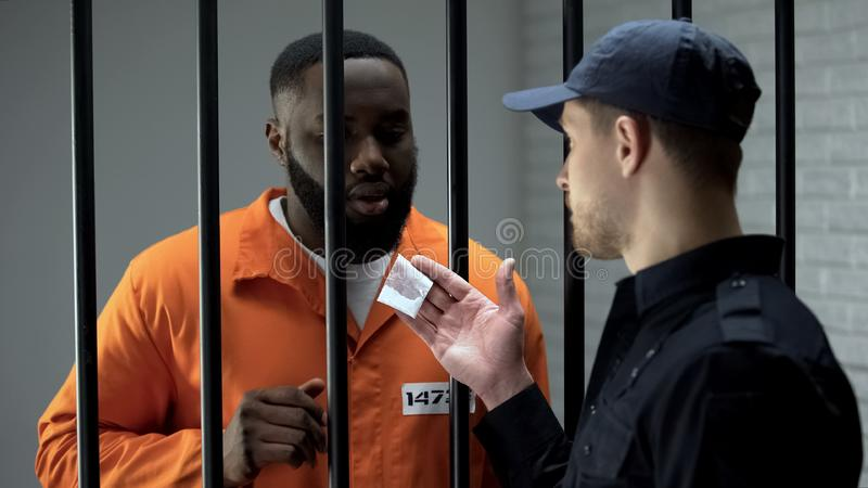 Prison guard giving black drug addicted male prisoner dose of white powder stock photography