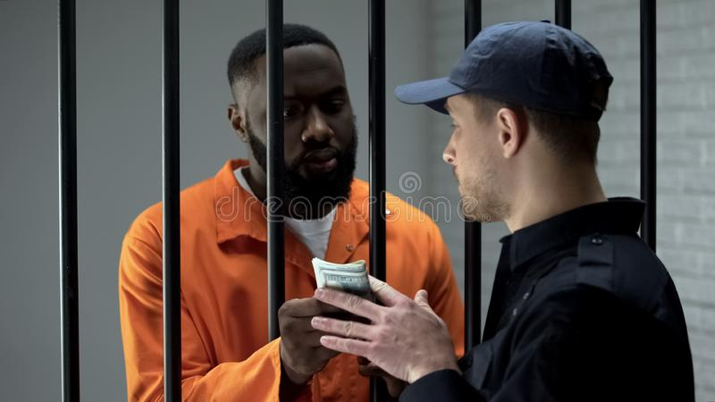 Prison guard taking dollar banknotes from afro-american criminal, corruption. Stock photo stock photos