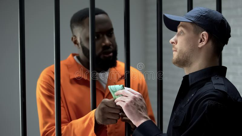 Prison guard taking euro banknotes from afro-american criminal, corruption. Stock photo royalty free stock photo