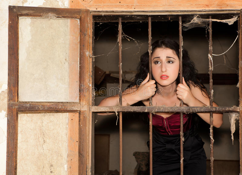 Prison sadness. Sad woman in prison behind bars of a derelict building stock photo