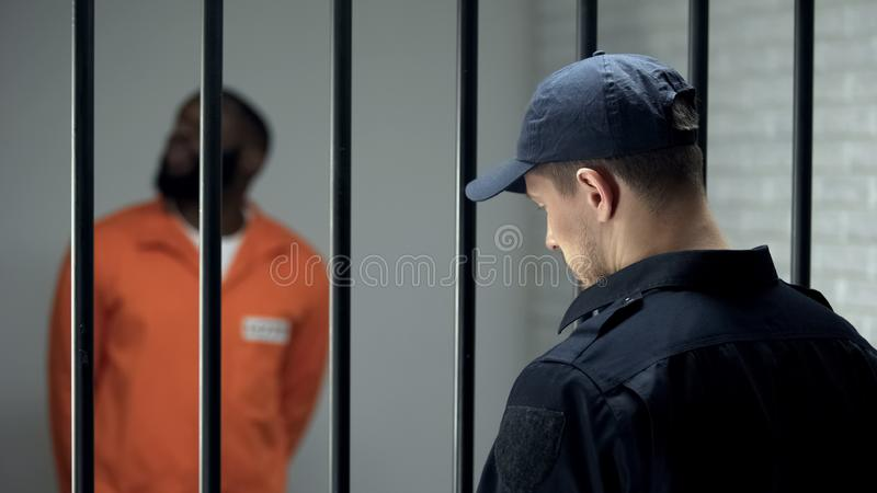 Prison security guard looking after dangerous criminal in cell, 24 hour guarding. Stock photo stock photos