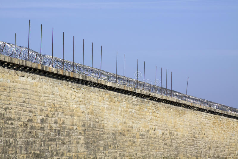 Prison wall. This is a photo of a brick prison wall with barbed wire royalty free stock image