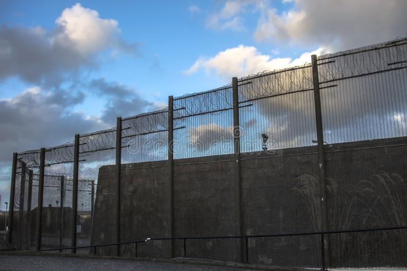 Prison walls and security fence. Peterhead, Scotland. Prison walls and security fence with spikes on the blue sky background. Peterhead Prison Museum, Scotland stock image