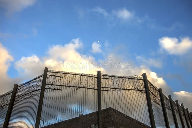 Prison walls and security fence. Peterhead, Scotland. Prison walls and security fence with spikes on the blue sky background. Peterhead Prison Museum, Scotland royalty free stock photos
