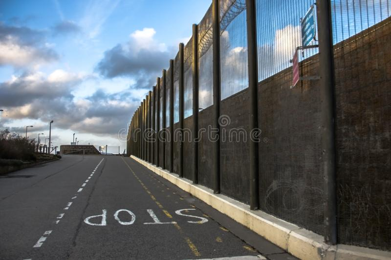 Prison walls and security fence. Peterhead, Scotland. Prison walls and security fence with spikes on the blue sky background. Peterhead Prison Museum, Scotland stock photos