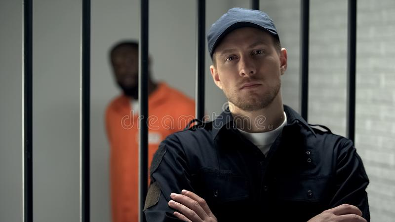 Prison warden looking to camera standing near cell with imprisoned afro-american royalty free stock photo