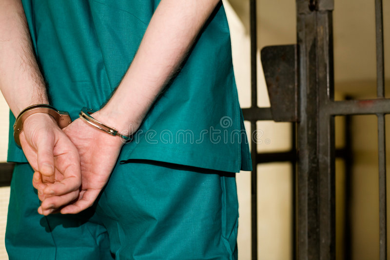 Prisoner. With handcuffs in the cell, crime concept stock photo
