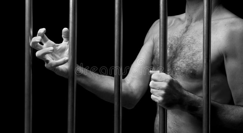 Prisoner behind bars royalty free stock photo