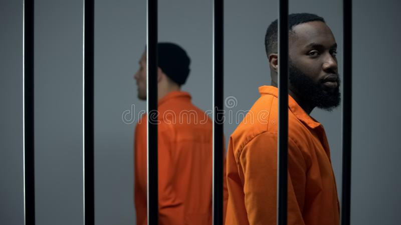 Prisoners walking in jail cell, long imprisonment, feeling hope for freedom royalty free stock images