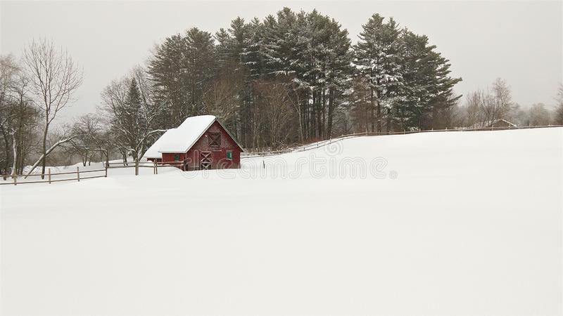 Pristine snowy field and red barn royalty free stock images
