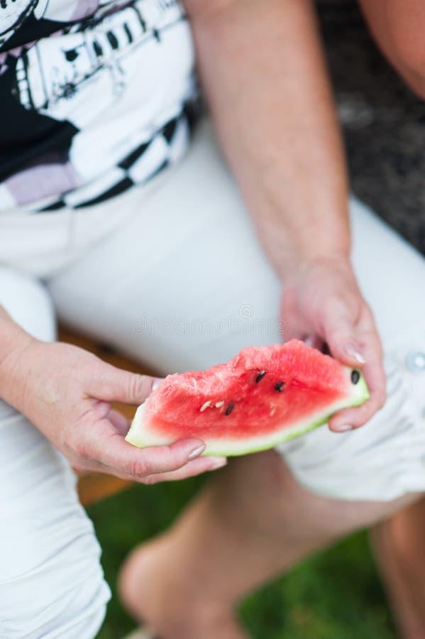Pritty-Frau h?lt Scheiben der Wassermelone auf einem dunklen Hintergrund Langsame Bewegung lizenzfreie stockbilder
