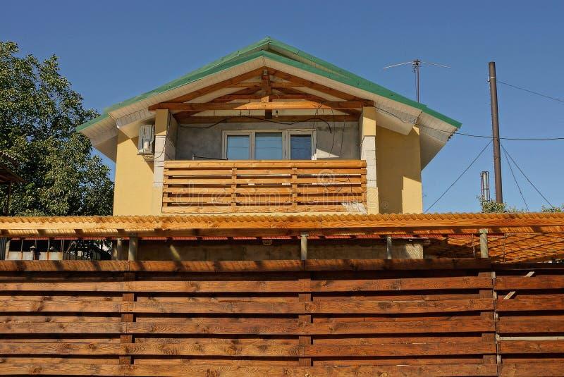 privé huis met een houten balkon en een venster achter een bruine omheining royalty-vrije stock afbeelding