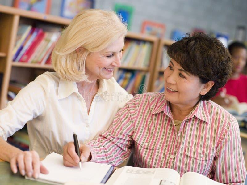 Privé-leraar die rijpe student bijstaat in bibliotheek stock fotografie