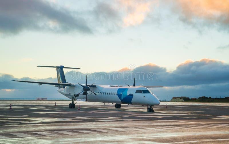 Privé propeller-gedreven vliegtuigparkeren bij de luchthaven met zonsondergangachtergrond royalty-vrije stock fotografie