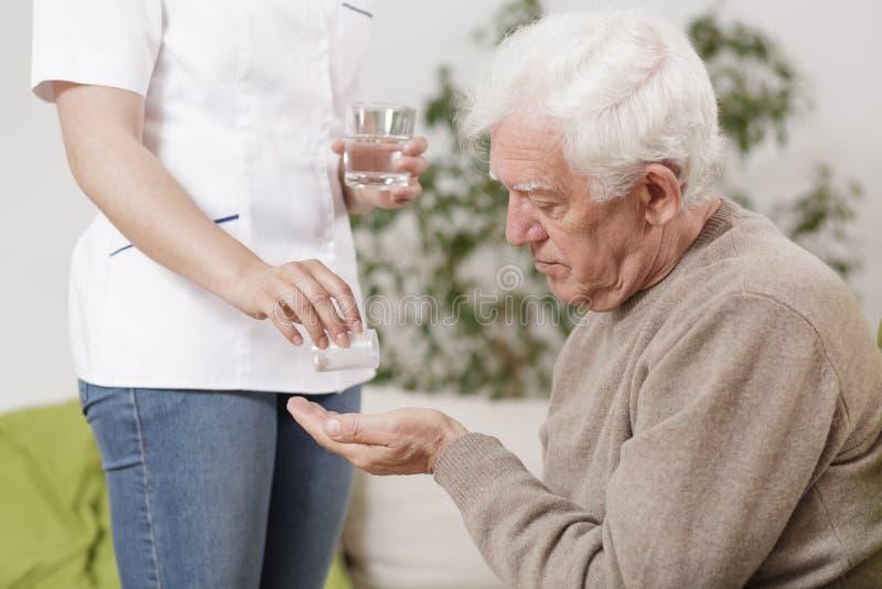 Privé verpleegster die geneesmiddelen geven royalty-vrije stock afbeeldingen