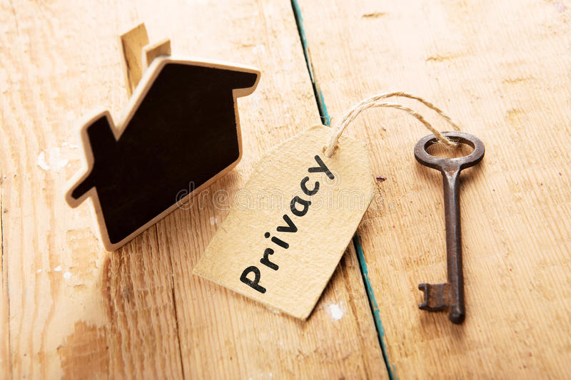Privacy concept - vintage key with tag with inscription. Privacy concept - little house and key with inscription on the wooden desk stock photos