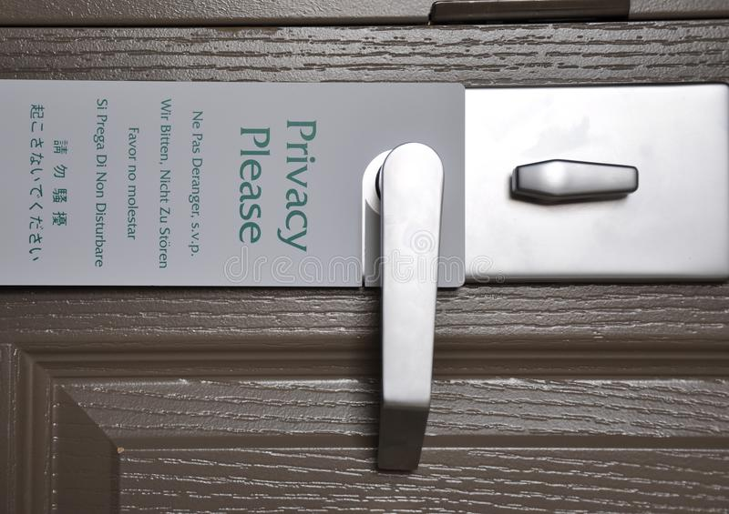 Privacy please sign. In different languages hanging in metallic door handle royalty free stock image