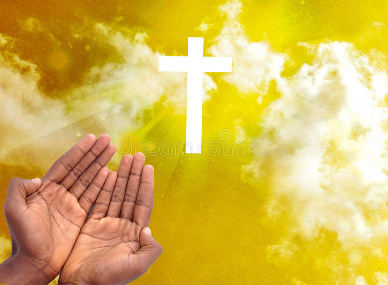 PRIVACY WITH SPIRITUAL CHRISTIAN CROSS. Male hands in spiritual intimacy before the Christian cross with rays of light in a yellow sky, wilt answer prayers royalty free stock photography