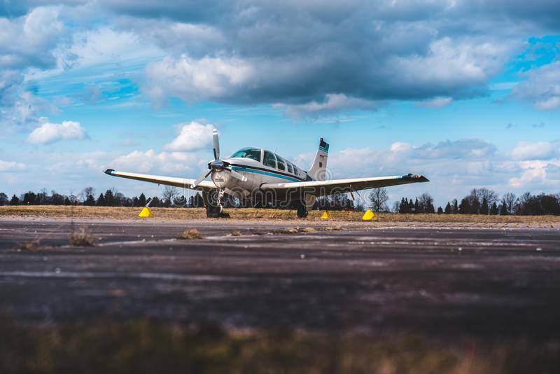 Privat Airplane on the road. Dramatic blue sky with clouds. stock images