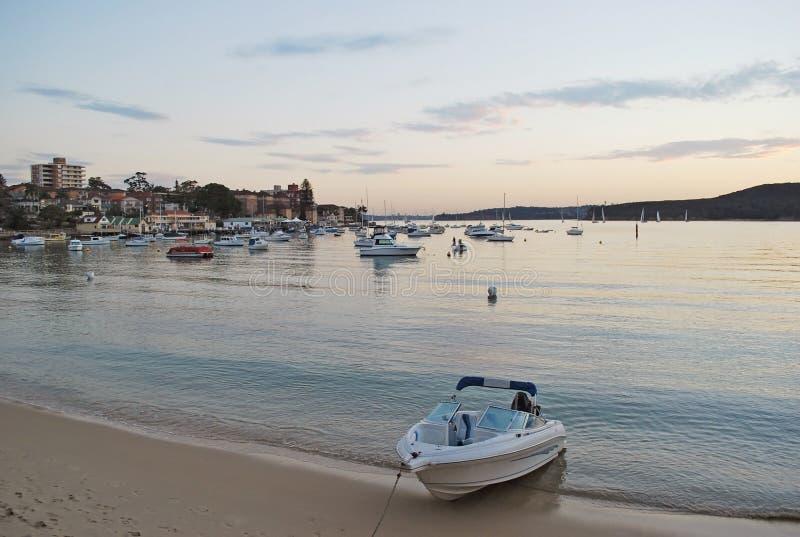 Privat fartyg på stranden på den manliga lilla viken under rosa solnedgång i Sydney arkivfoton