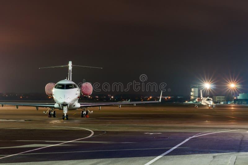 Privat jet som parkeras i flygplatsen på natten lopp för timezone för tid för affärsklockabegrepp olikt visande arkivfoto