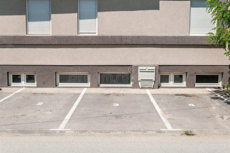 Privat parkeringsplatsutrymme för bilar med reservation numrerar framme av den bostads- byggnaden i staden royaltyfria bilder