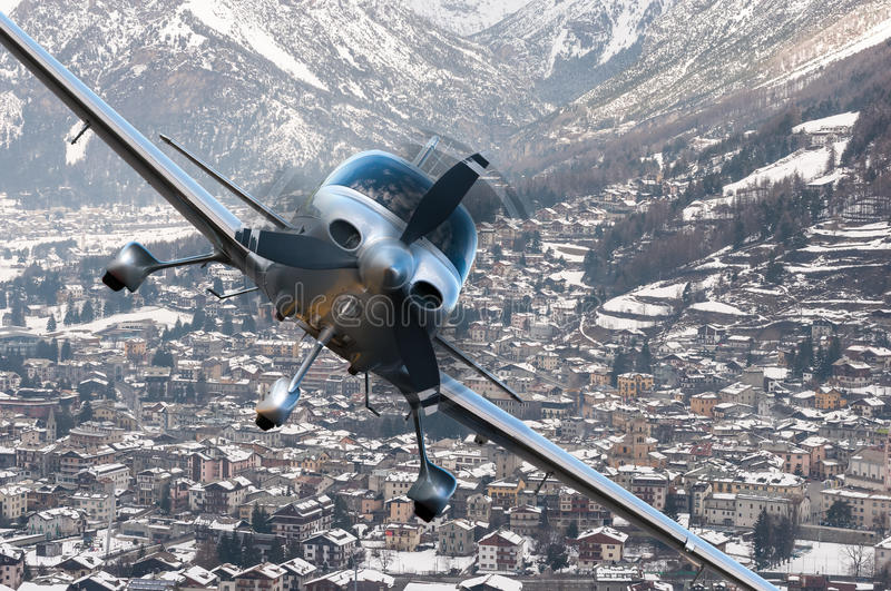 Privat plane or aircraft flight above winter resort city, village surrounded by mountains royalty free stock image