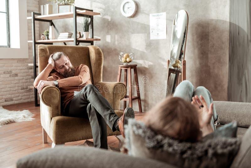 Privat terapeut som bär den orange polohalsen som talar till klienten arkivbild