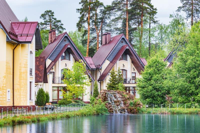 Privata lyxiga hus vid sjön i skogen på regnig tid för vårdag royaltyfri fotografi