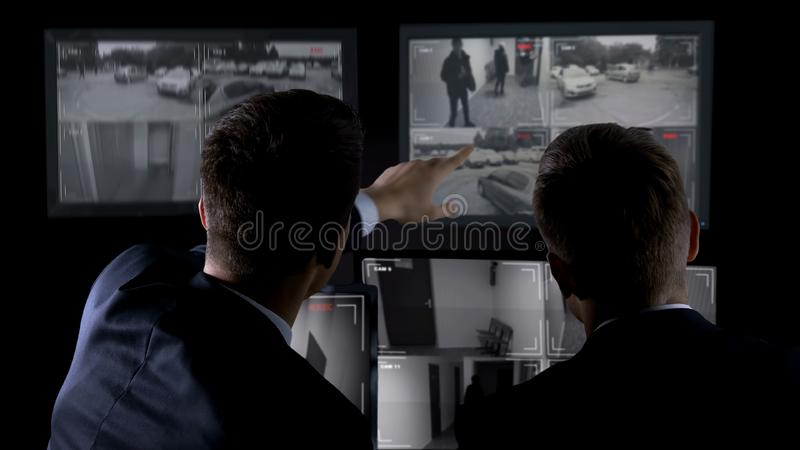 Private agents monitoring CCTV footage, searching for criminal, discussion. Stock photo stock photo