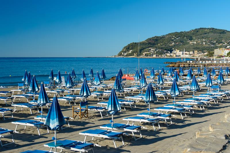 Private beach equipped with blue deckchairs and beach umbrellas royalty free stock photography