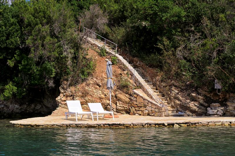 Private beaches on mediterranean sea. Chairs, deck chairs, sun loungers and parasols waiting for tourists. royalty free stock image