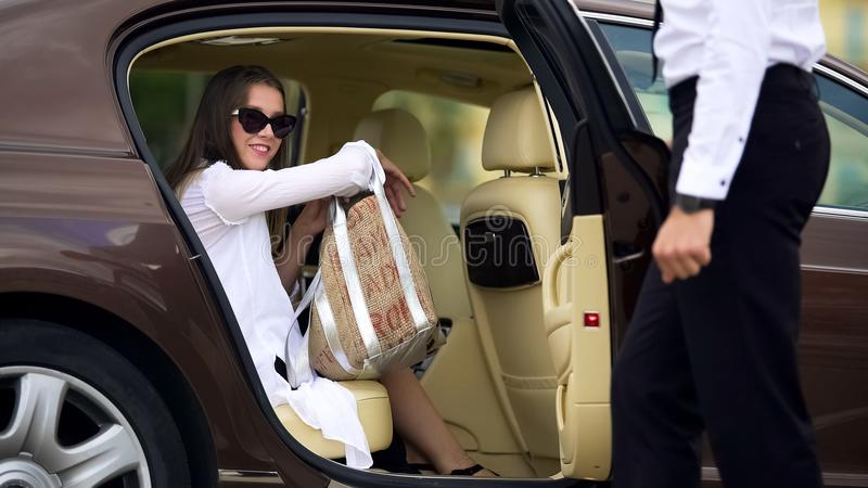 Private chauffeur opening door for beautiful female passenger, car services stock images