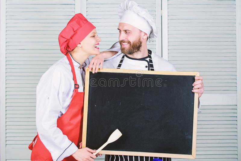 Private cooking school. Master cook and prep cook giving cooking class. Chef and cook helper teaching master class. Couple of men and women holding empty stock photography