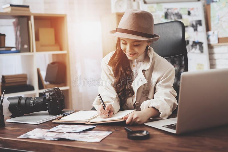Private detective agency. Little girl is sitting at desk taking notes in notebook. stock image