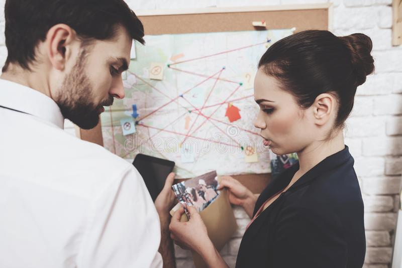 Private detective agency. Man and woman are looking at map, discussing clues. stock photo
