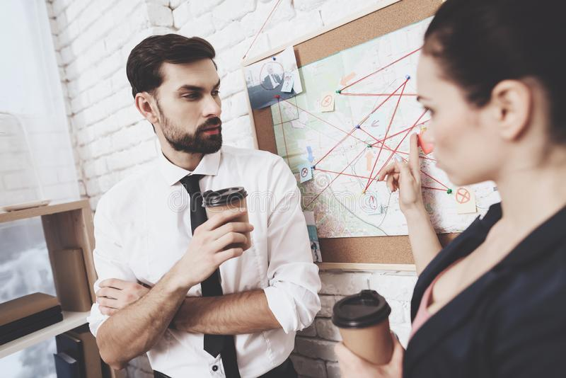Private detective agency. Man and woman are looking at clues map, drinking coffee. royalty free stock photography