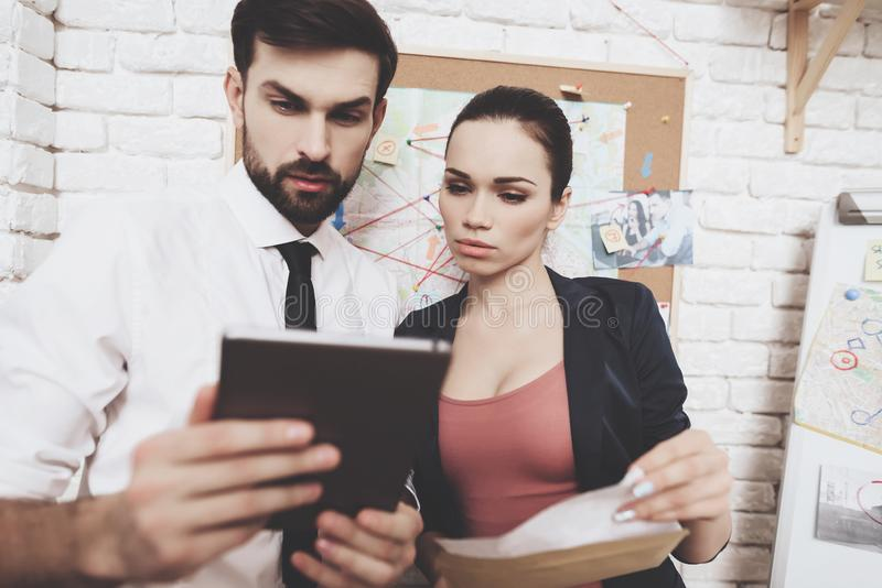Private detective agency. Man and woman are looking at clues on tablet in office. stock images